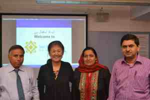 Liz Tu and AIOU faculty at Universal Design for Learning and Accessibility Workshop (note Urdu welcome on screen behind!)